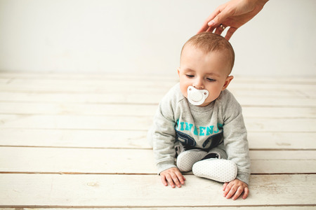 one year old: One year old cute baby boy sitting on rustic wooden floor over white background Stock Photo