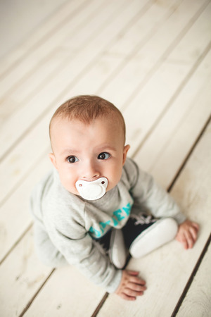 One year old cute baby boy sitting on rustic wooden floor over white