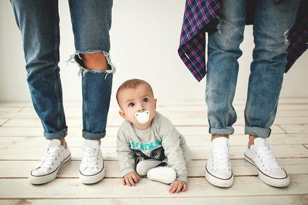 Jonge hipster vader moeder en schattige baby jongen op rustieke houten vloer over wit