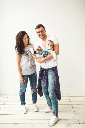 Jonge hipster vader moeder bedrijf schattige baby jongen op rustieke houten vloer over wit