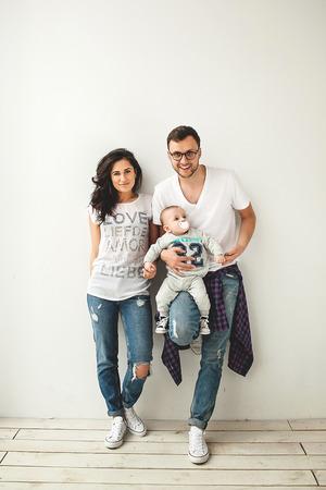 흰색 배경 위에 소박한 나무 바닥에 귀여운 아기 소년을 들고 젊은 힙합 아버지의 어머니 스톡 콘텐츠 - 39343574