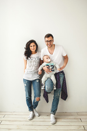 Jeune maman hipster père tenant mignon petit garçon sur le plancher en bois rustique sur fond blanc Banque d'images - 39343574