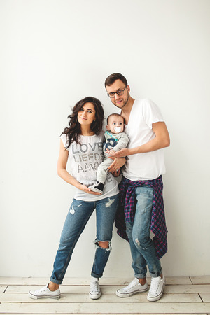 Young hipster father mother holding cute baby boy on rustic wooden floor over white