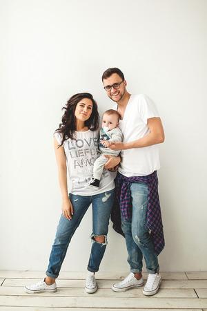 Jonge hipster vader moeder bedrijf schattige baby jongen op rustieke houten vloer over een witte achtergrond Stockfoto