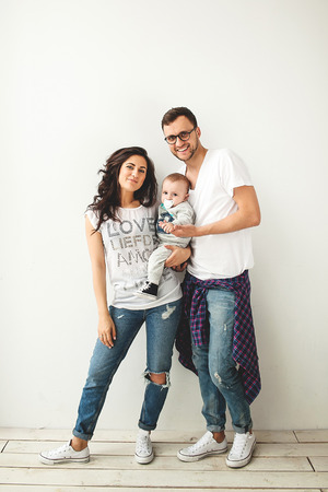 Young hipster father mother holding cute baby boy on rustic wooden floor over white background