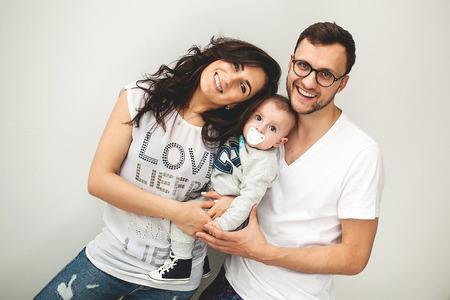 Jeune maman hipster père tenant mignon petit garçon sur le plancher en bois rustique sur fond blanc Banque d'images - 39343601