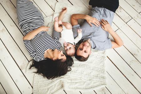 幸せな若い父、母、素朴な木製の床で横になっているかわいい男の子 写真素材