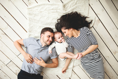 Happy young father mother and cute baby boy lying on rustic wooden floor