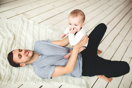Young happy father holding son in hands lying on rustic wooden floor Zdjęcie Seryjne - 39343581