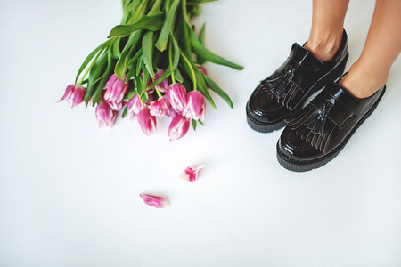 brogues: Fine trendy black leather brogues on women legs with flowers and copy space