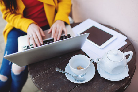Woman hands in bright clothes with laptop tablet and tea outdoors in cafe