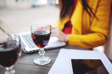 Woman works with glass of red wine tablet and laptop in street cafe