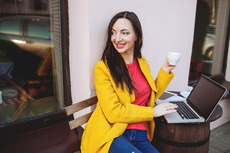 Woman in bright clothes with laptop tablet and tea outdoors in cafe photo