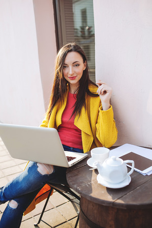 Young brunette woman in bright clothes with laptop tablet and tea outdoors in cafe photo