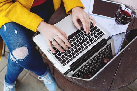 mujeres trabajando: Manos de mujer escribiendo en la computadora portátil, tableta y el vino rojo al aire libre en el café