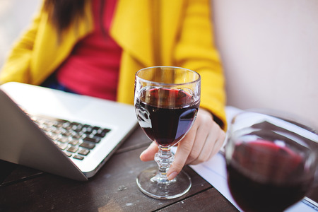 女性の手のグラスの赤ワイン タブレットやカフェでノート パソコンと