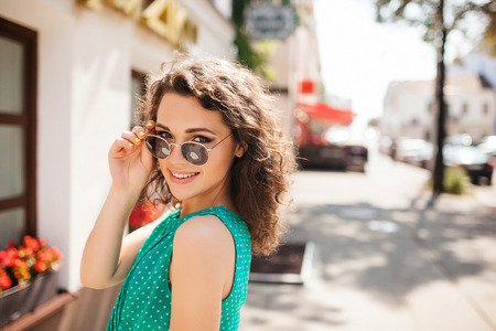 Jeune femme en lunettes de soleil rondes et la robe aux cheveux bouclés sourire sur l'épaule dans la rue de la ville Banque d'images - 39464882