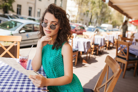 Young beautiful woman in round sunglasses with curly hair with cocktail making an order at the terrace of cafe photo