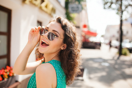 Young woman in round sunglasses and dress with curly hair smiling over the shoulder in the city street