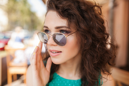 Young beautiful woman in round sunglasses with curly hair with cocktail making an order at the terrace of cafe