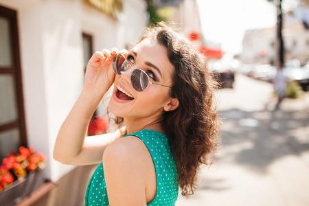 도시 거리에서 어깨 너머로 미소 곱슬 머리를 가진 젊은 라운드 선글라스 여자와 드레스
