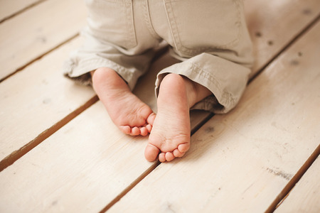 Legs of baby in pants on wooden floor Stok Fotoğraf