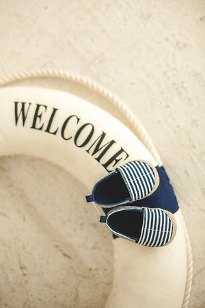 Lifebuoy and blue baby booties in stripes on a light background Stockfoto