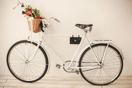 mocks: White retro bicycle on white wooden floor with basket full of flowers Stock Photo