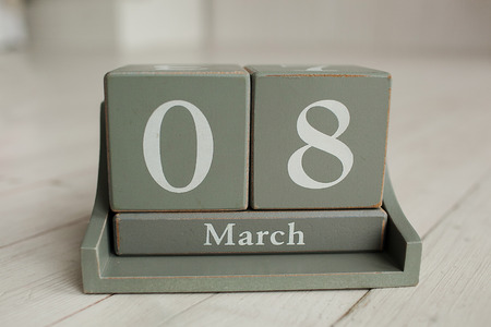 8 march: Wooden calendar with 8 March and floowers on white background greeting card