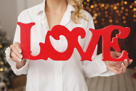one female: Woman holding love letters as a Valentines gift in room with decorated background