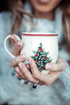 legwarmers: Christmas cup with tree in hands of young woman