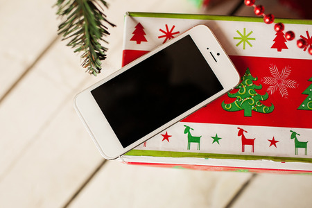 White smartphone with the christmas tree in background photo