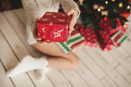 white socks: Beautiful woman legs in socks and decorated Christmas tree with gifts Stock Photo