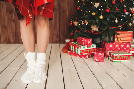 Beautiful woman legs in socks and decorated Christmas tree with gifts photo