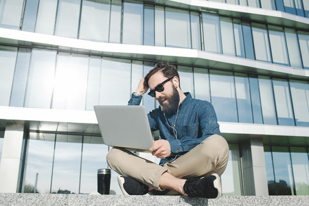 young hipster businessman with beard in sunglasses with laptop holding his head outdoors in front of office building photo