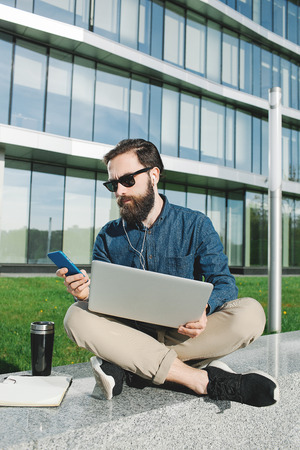 young hipster businessman with beard in sunglasses with laptop making a call outdoors in front of office building photo