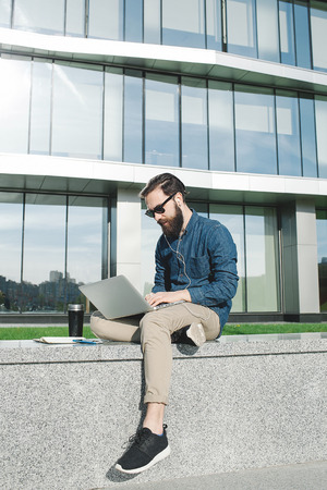 busy beard: young hipster businessman with beard in sunglasses work with laptop outdoors in front of office building