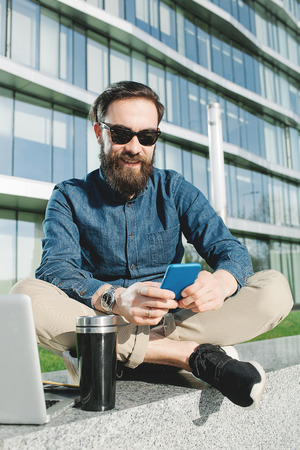 Young hipster in sunglasses and beard making selfie with coffee outdoors in the city photo