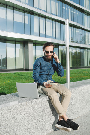 young hipster businessman with beard in sunglasses with laptop talking phone outdoors in front of office building photo
