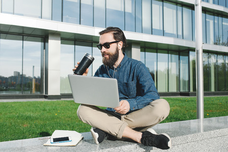 young hipster businessman with beard in sunglasses with laptop drinking coffee outdoors in front of office building photo