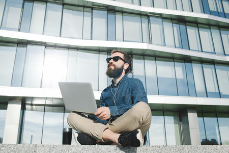 young hipster businessman with beard in sunglasses work with laptop outdoors in front of office building photo