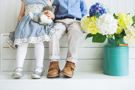 Baby boy and girl with toy sitting on a wooden floor with flowers