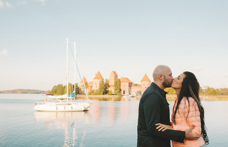 Young couple kissing near historic castle on vacation in Europe photo