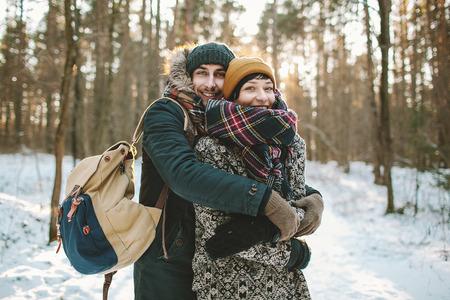 バッグを持った若い男が冬の森で彼のガール フレンドを抱擁します。
