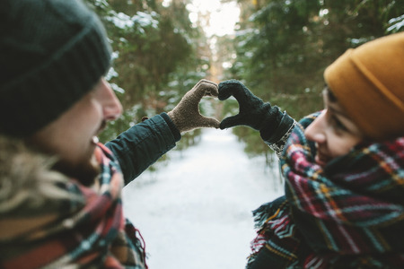 snow white: Young hipster couple holding hands in love heart symbol in winter forest