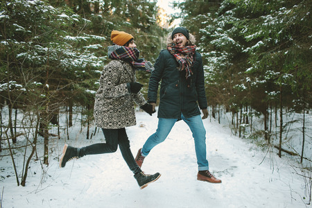 couple winter: Young hipster couple having fun jumping in winter forest Stock Photo