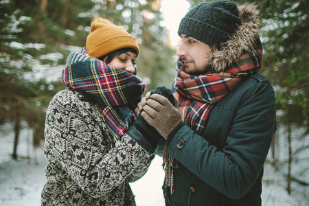 winter couple: Young hipster couple having a date in winter forest Stock Photo