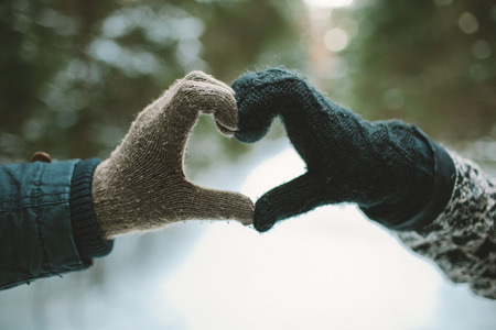 Two hands in gloves holding love heart symbol in winter forest