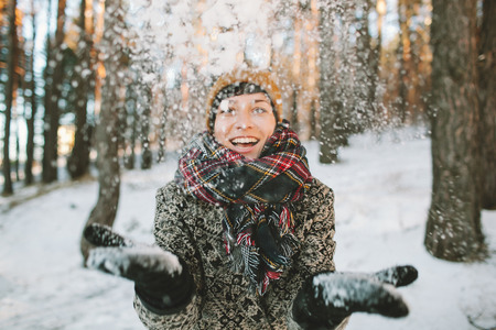 Young hipster woman in winter forest having fun with snow falling in hands Stockfoto