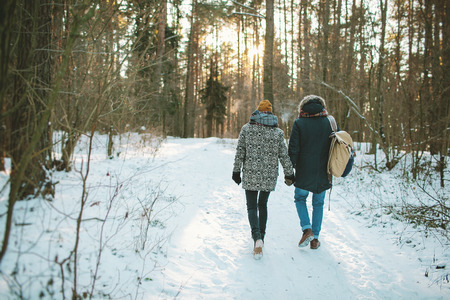 Young hipster couple having a walk in winter forest with bag alone